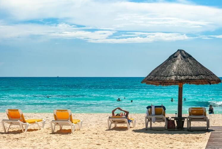 Tropikalna plaża z leżakami i morzem – koronawirus a lot samolotem